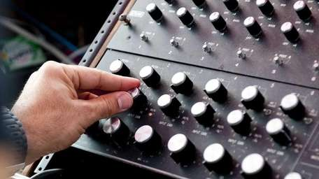 A DJ adjusts the knobs on a mixer
