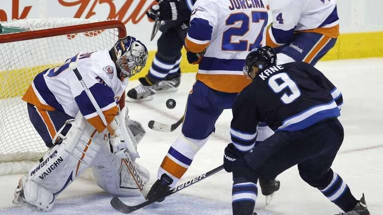 Islanders goaltender Evgeni Nabokov watches the puck as