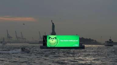 A boat carrying an advertising board sails past