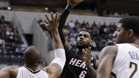 Miami Heat forward LeBron James, center, shoots over
