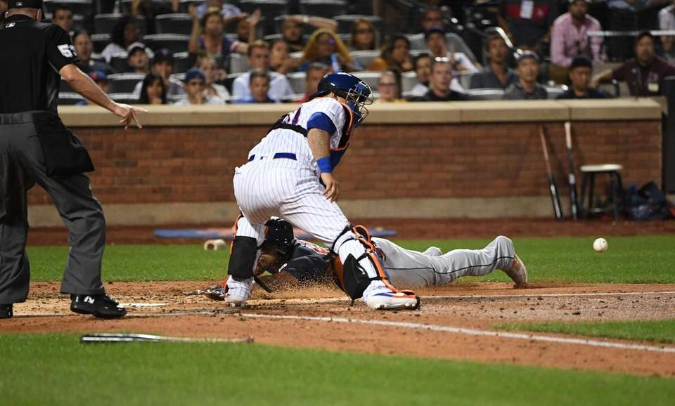 Cleveland Indians' Yasiel Puig slides home as New