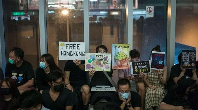 Protesters take part in a sit-in in Yuen