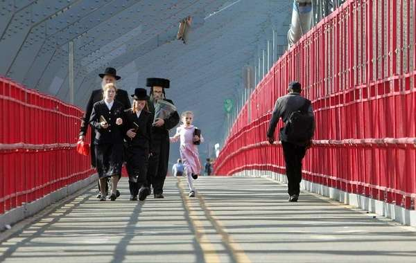 Hasidic Satmar Jews walk across the Williamsburg Bridge