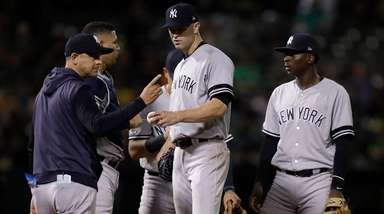 Yankees pitcher J.A. Happ hands the ball to