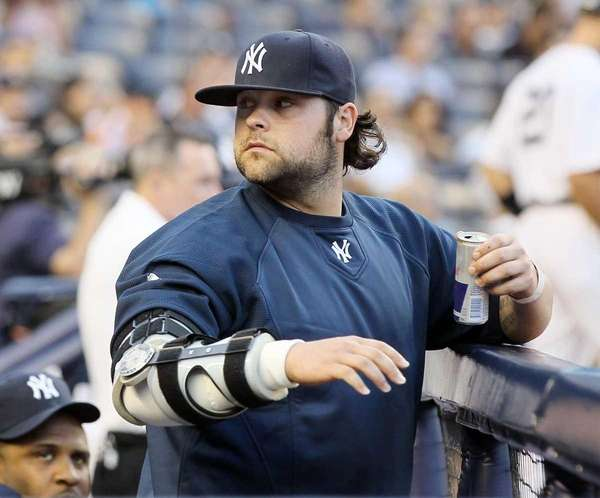 Injured pitcher Joba Chamberlain looks on from the