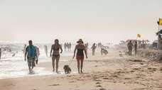 People walk along the beach at Kismet on