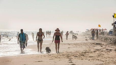 People walk along the beach at Kismet on