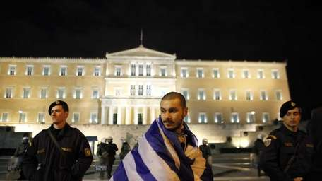 A protester wearing a Greek national flag stands