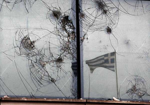 A Greek flag is reflected on smashed windows