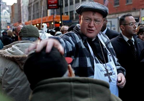 Cardinal Timothy Dolan speaks to a man who