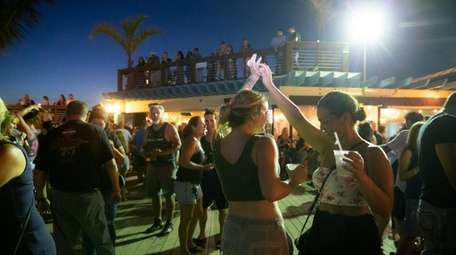 Beachgoers dance to live music outdoors at Salt