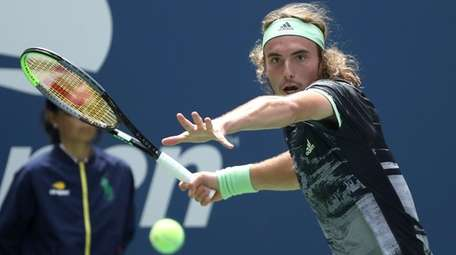 Stefanos Tsitsipas returns a shot to Andrey Rublev