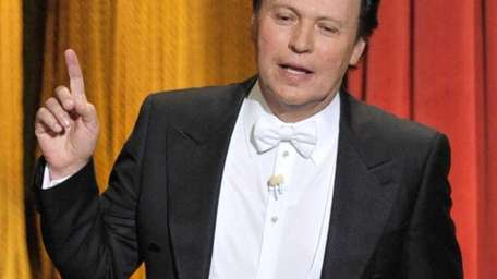 Host Billy Crystal performs onstage during the 84th