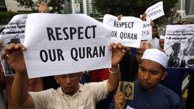 Muslim protesters hold placards during a protest against
