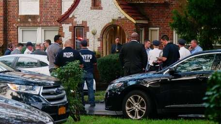 Police gather outside the Laurelton home of an