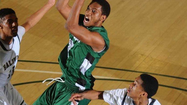 Elmont High School #3 Michael Dugue, center, attempts