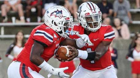 Stony Brook's quarterback Tyquell Fields hands off to