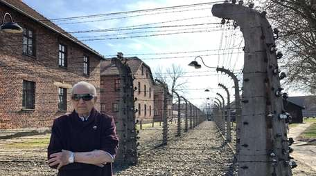 Irving Roth is seen in front of Auschwitz
