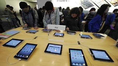 Customers look at Apple iPads.