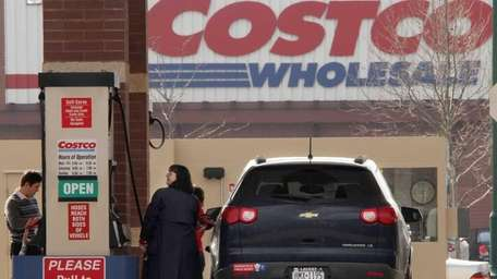 Costco members pump gas outside a Costco Wholesale