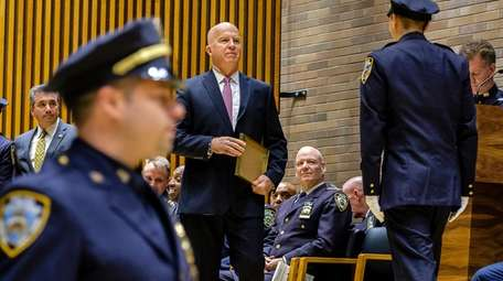NYPD Commissioner James O'Neill, center, greets officers during