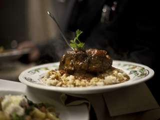 Veal osso buco is served on a bed