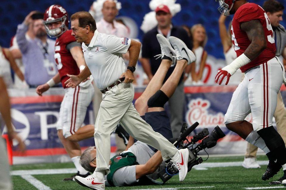 A cameraman falls as Alabama head coach Nick