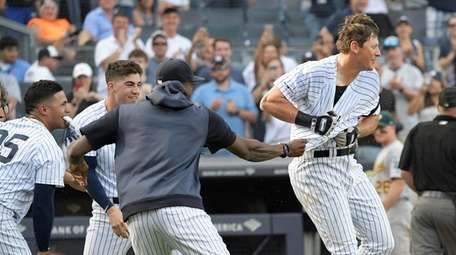DJ LeMahieu is mobbed by his Yankees teammates