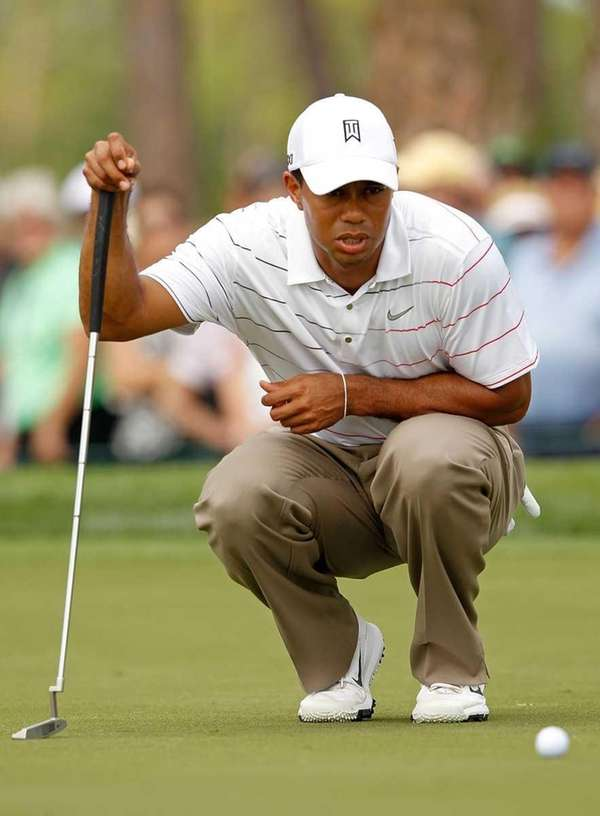 Tiger Woods lines up a putt on the