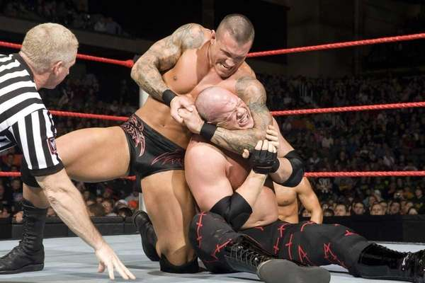 Professional wrestler Randy Orton gives his opponent, Kane,