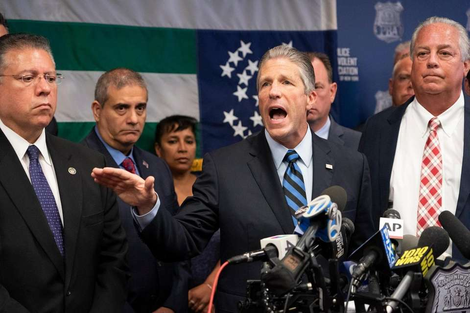 Police Benevolent Association President Patrick Lynch, center, holds