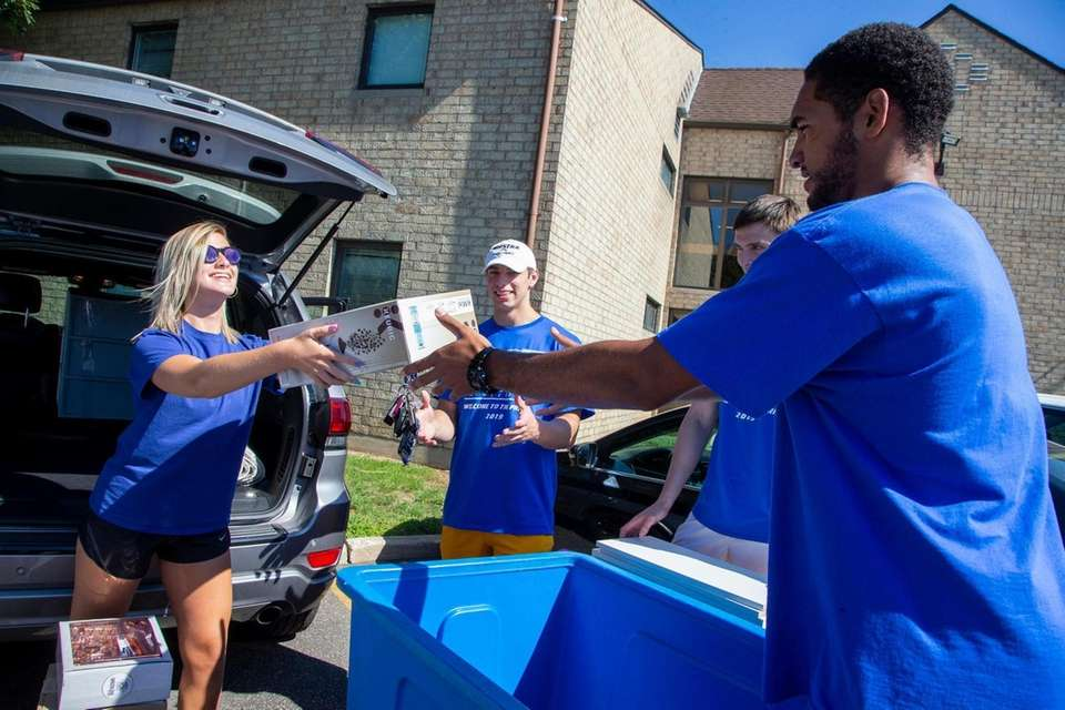 Madison Snuffer, center, unloads her car with the