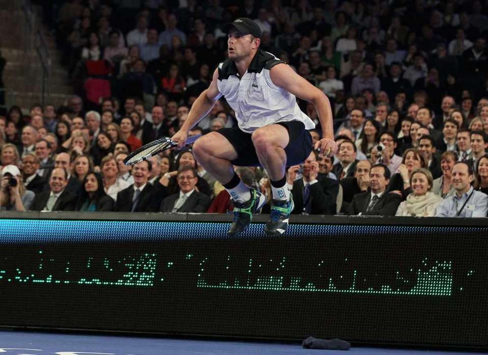Andy Roddick in action against Roger Federer during