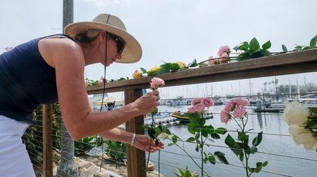 Maya Upton, of Santa Barbara, Calif., places flowers