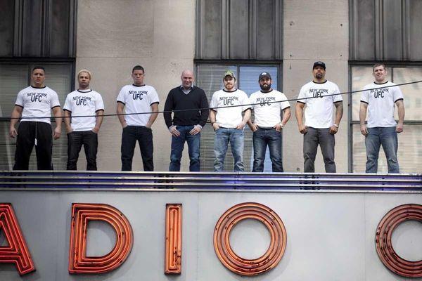 UFC president Dana White (black sweater) poses with