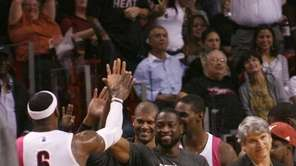 Miami Heat's LeBron James celebrates with teammates, from
