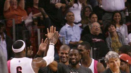 Miami Heat's LeBron James celebrates with teammates, from