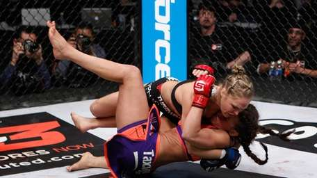 Ronda Rousey, top, and champion Miesha Tate fight
