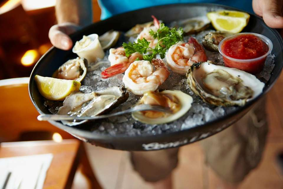 A tray of raw oysters and shrimp at