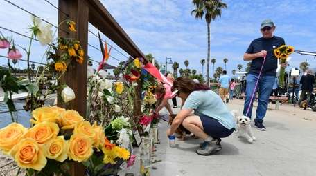 A woman places a flower at makeshift memorial