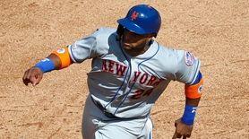The Mets' Robinson Cano runs to third base