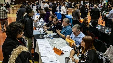Job seekers meet recruiters at a job fair
