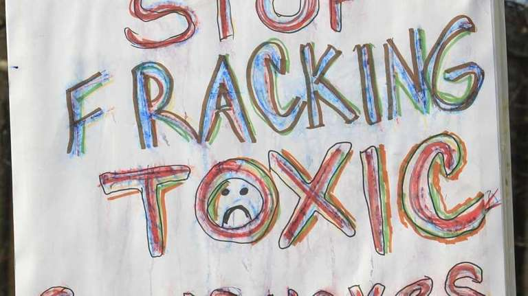 A protester holds up a sign against fracking