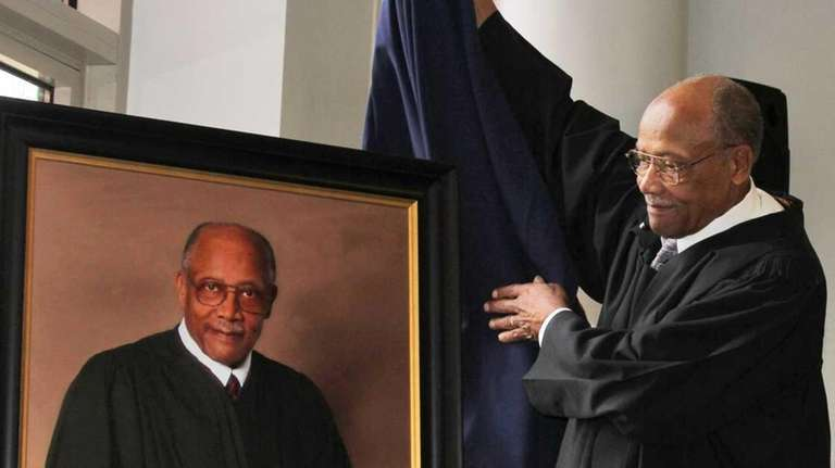 Retired Justice Marquette Floyd lifts the covering off