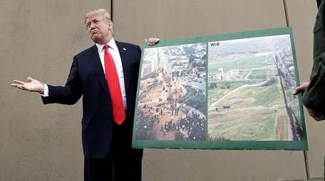 President Donald Trump holds a poster with photographs