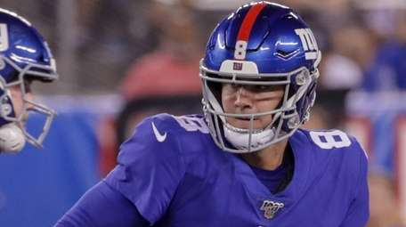 Giants quarterback Daniel Jones looks to hand off