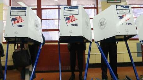 Voters cast their ballots at voting booths at