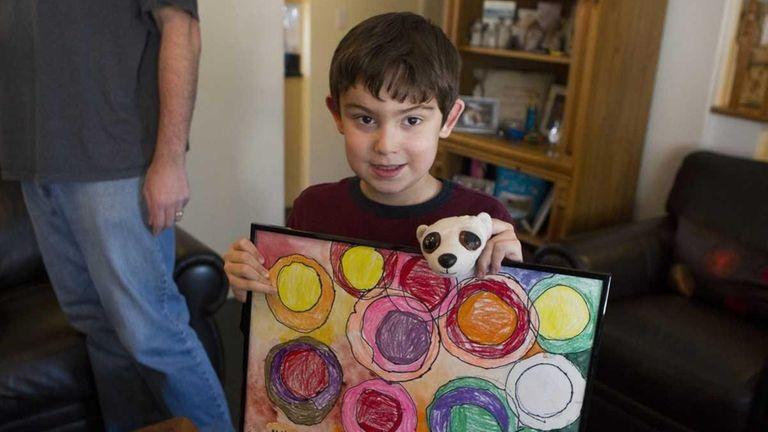 Michael Augello holds up his original artwork used