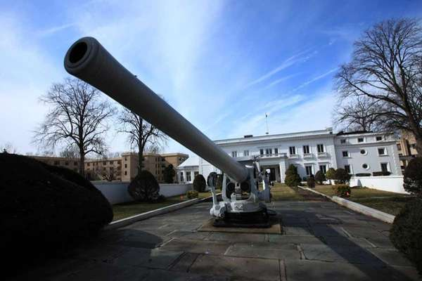 A historic naval gun marks the approach to