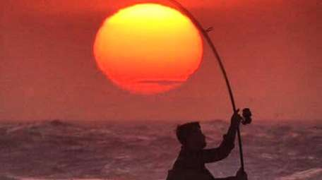 A surf caster fishing for striped bass at